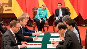 Chancellor Angela Merkel and China's Prime Minister Li Keqiang look on as agreements are signed.