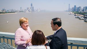 Chancellor Angela Merkel talks to the Provincial Governor on a bridge over the Chang Jiang River.