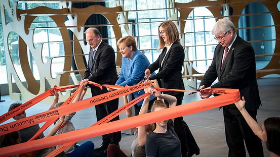 Chancellor Angela Merkel and other guests of honour cut the red tape to officially open the Bauhaus Museum in Dessau.