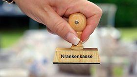Ein Holzstempel mit der Aufschrift Krankenkasse, gehalten von einer weiblichen Hand.
