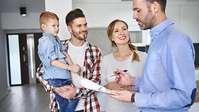 Ein Makler zeigt einem jungen Paar mit Kind eine Wohnung.