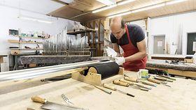 Orgelbauer beim Aufschneiden einer Orgelpfeife