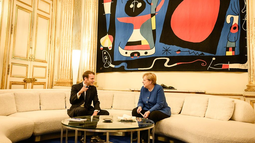 President Emmanuel Macron and Chancellor Angela Merkel in conversation on a semi-circular cream sofa, against the backdrop of a dramatic painting