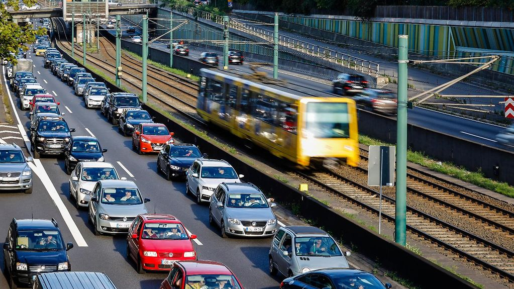 A tram drives along its rails beside two lanes of slow-moving cars on a road.