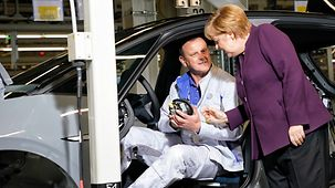 Chancellor Angela Merkel talks to an employee during a tour of Volkswagen's Zwickau plant.