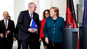 Chancellor Angela Merkel walks beside Christoph Schmidt, Chairman of the German Council of Economic Experts.