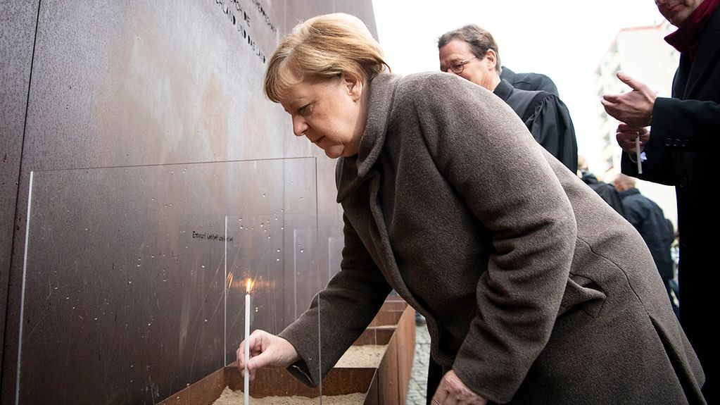The photo shows the Chancellor lighting a candle in memory of the victims.