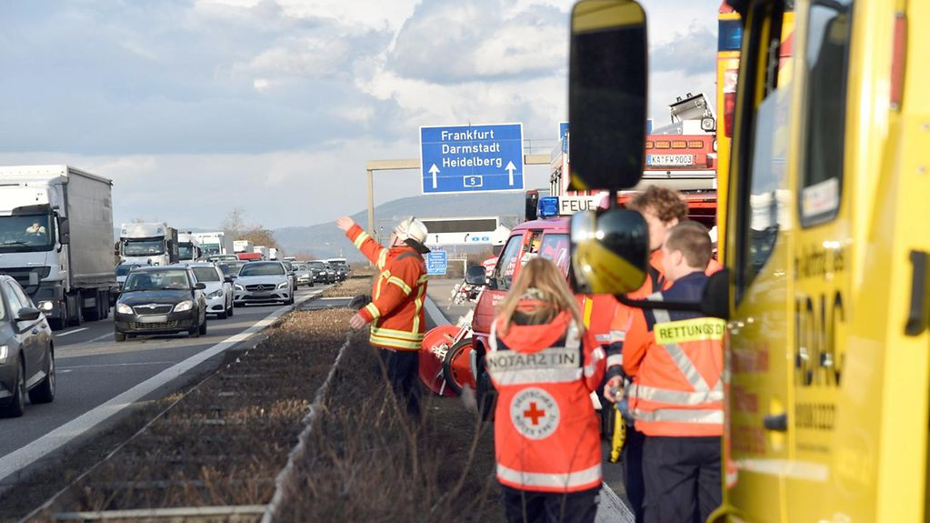 Emergency services at the scene of a motorway accident. One officer waves at traffic on the opposite carriageway to move on.
