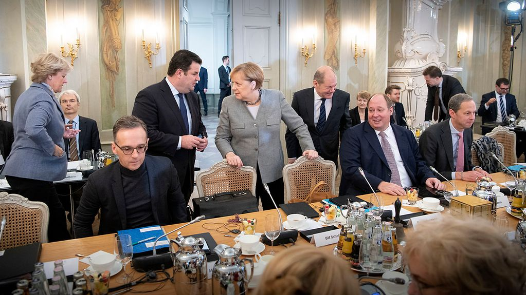 Chancellor Angela Merkel talks with Hubertus Heil, Federal Minister of Labour and Social Affairs, during the Cabinet retreat at Schloss Meseberg