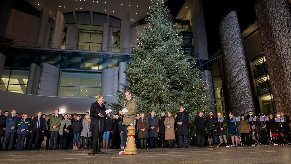Chancellor Angela Merkel is presented with the traditional Christmas trees at the Federal Chancellery.
