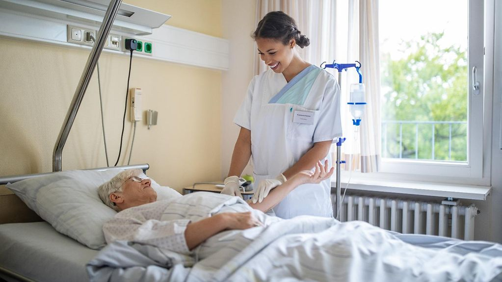 A nurse beside a patient's bed