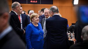 Chancellor Angela Merkel in conversation with Lower Saxony's state premier Stephan Weil