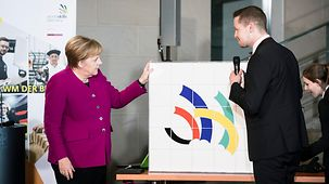 Chancellor Angela Merkel talks to a participant at the reception for the German WorldSkills team.