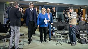 Chancellor Angela Merkel and Markus Söder, Bavarian state premier on the way to meet the press