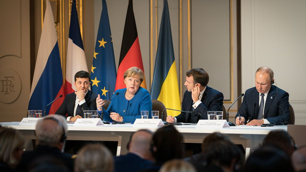 Chancellor Angela Merkel speaks at a press conference, where she sits with Volodymyr Zelensky, President of Ukraine, Emmanuel Macron, French President, and Vladimir Putin, Russian President.