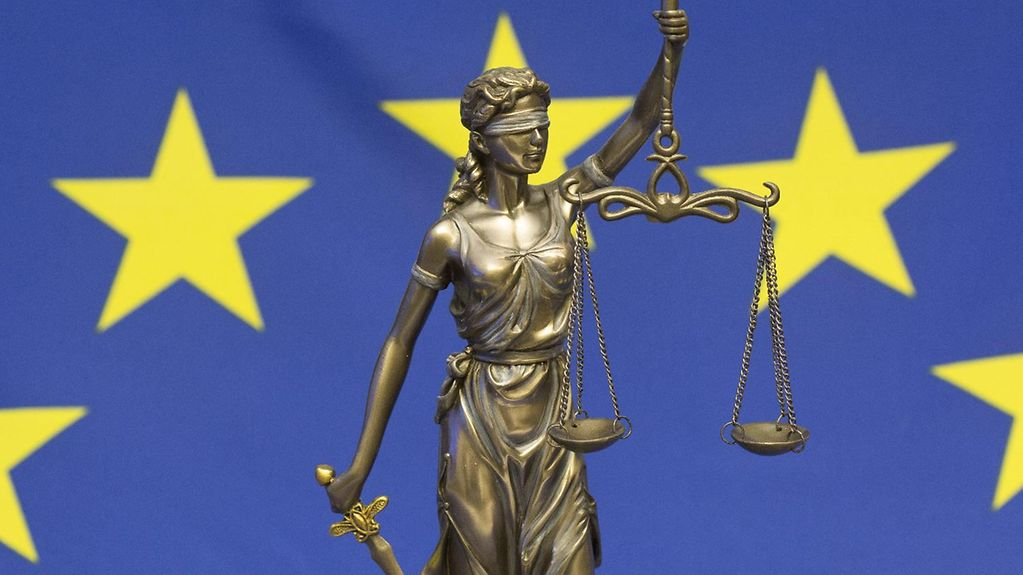 Bronze statue of the Roman goddess Justitia against the background of an EU flag