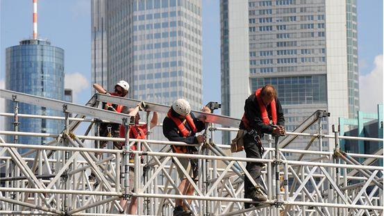 Workers put up scaffolding for a stage on the banks of the River Main in Frankfurt am Main.
