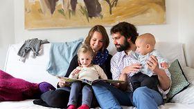 Junge Familie liest gemeinsam ein Bilderbuch auf dem Sofa.