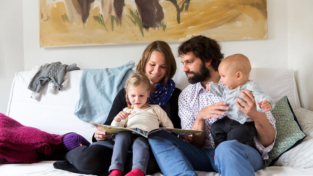 A young family reads a storybook together on the sofa.
