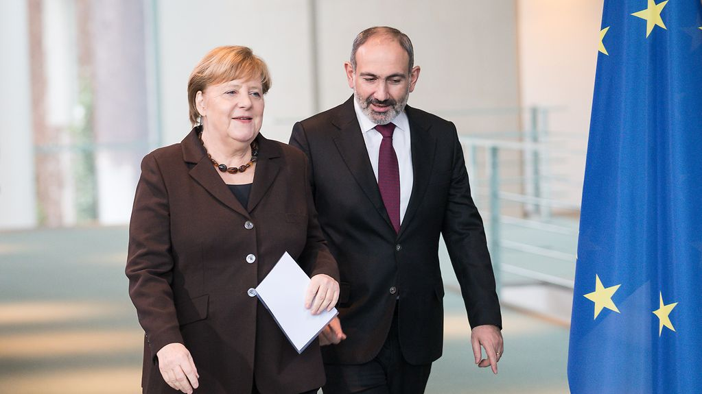 Chancellor Angela Merkel and Prime Minister Nikol Pashinyan beside an EU flag