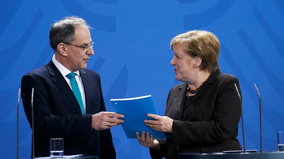 Uwe Cantner, Chairman of the Commission of Experts for Research and Innovation, presents Chancellor Angela Merkel with the Commission's annual report.