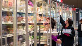 Mitarbeiterinnen in einem Supermarkt tragen Schutzmasken, während sie Regale auffüllen.