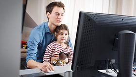 Ein junger Mann sitzt mit einem jungen Mädchen an einem Schreibtisch und schaut auf einen Computer.