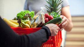 Ein Einkaufkorb mit Lebensmitteln wird an einer Tür überreicht.