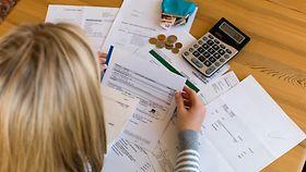 Ein Frau sitzt an einem Schreibtisch, auf dem Tisch liegen Rechnungen, ein Taschenrechner und eine offene Geldbörse mit Kleingeld.