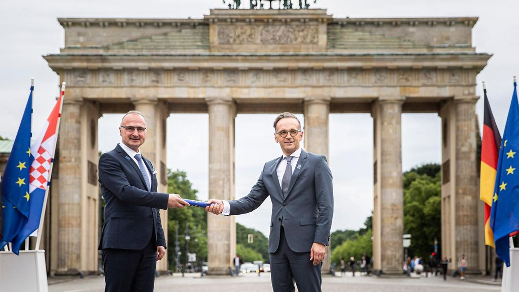 At the Brandenburg Gate, Federal Minister for Foreign Affairs Heiko Maas (at right) is handed the symbolic baton by his Croatian counterpart Gordan Grlić Radmann.