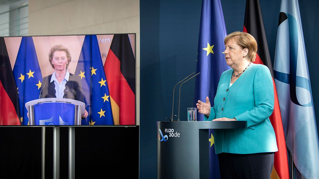 Chancellor Angela Merkel gives a press conference; European Commission President Ursula von der Leyen can be seen on a monitor next to the Chancellor.