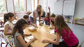 Foto zeigt Grundschulkinder mit einer Lehrerin.