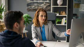 Das Bild zeigt das Büro eines Bürgeramtes: Eine Mitarbeiterin berät einen Bürger.