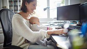 Lächelnde Mutter sitzt am Schreibtisch vorm Computer mit Baby auf dem Schoß.