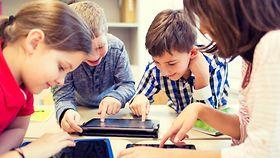 Foto zeigt Kinder, die auf ein Tablet schauen
