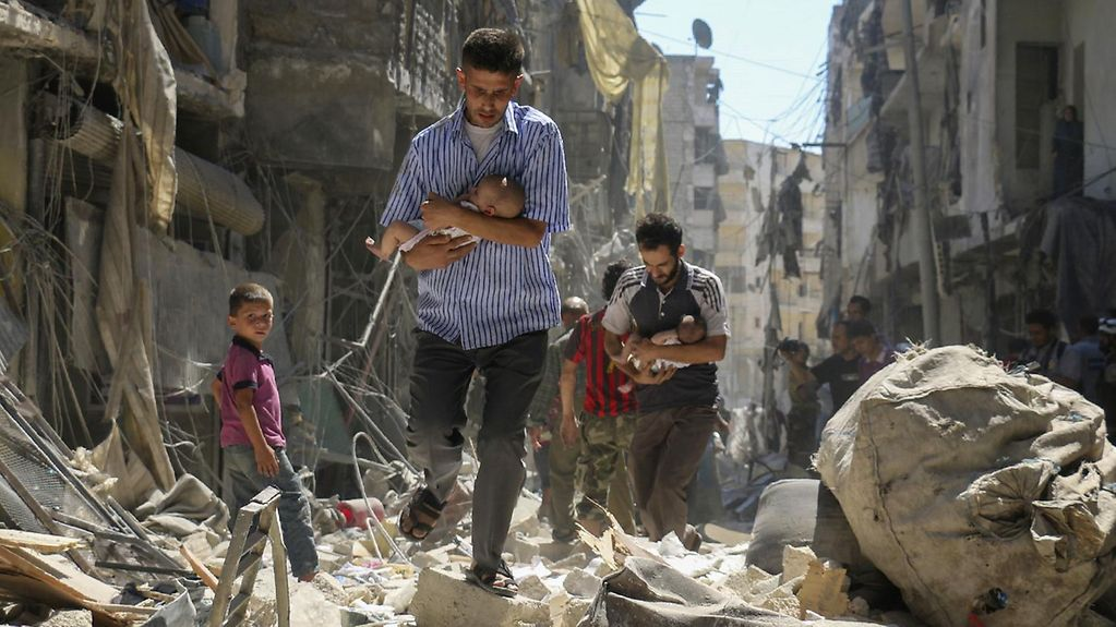 In Syria, a man rescues a small child from a pile of rubble.