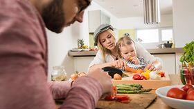 Eine Familien bereitet gemeinsam das Essen zu.