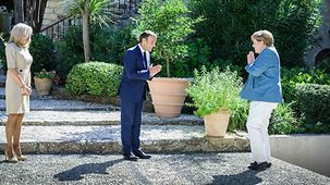 Chancellor Angela Merkel and French President Emmanuel Macron greet one another.