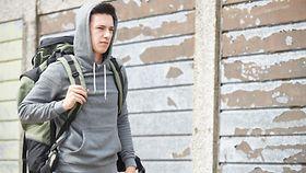 Ein junger Mann mit Kapuzenpullover und Rucksack auf der Straße.