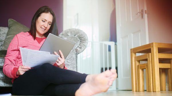 Eine junge Frau sitzt auf dem Fußboden ihres Wohnzimmers. Sie betrachtet ein Tablet und betrachtet Kontoauszüge.