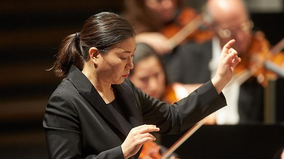 A woman conductor sets the pace.