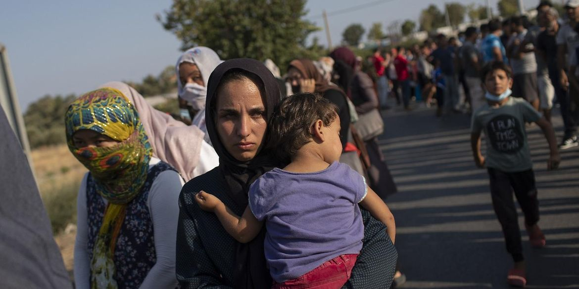 A woman holds her baby in her arms, and waits for help along with many other migrants on the Greek island of Lesbos.
