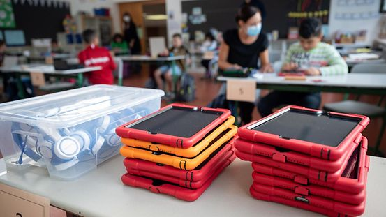 Tablets piled on a desk in a primary school classroom