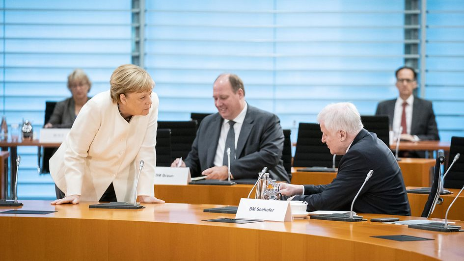 Chancellor Angela Merkel in discussion with Horst Seehofer, Federal Minister of the Interior, Building and Community, at the start of the Cabinet meeting