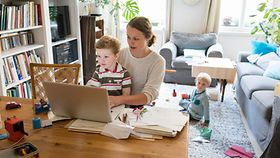 Foto zeigt eine Frau mit Laptop und Kind auf der Schoß