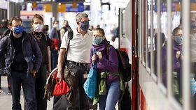 Reisende mit Masken auf dem Bahnsteig