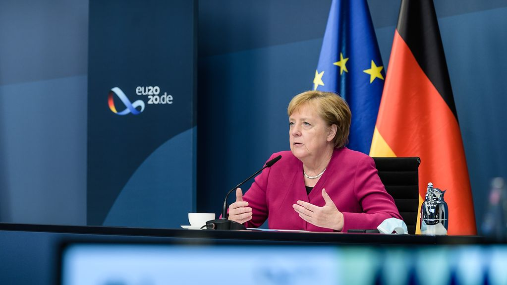 Chancellor Angela Merkel at a desk in the Federal Chancellery during a video conference of the Tripartite Social Summit