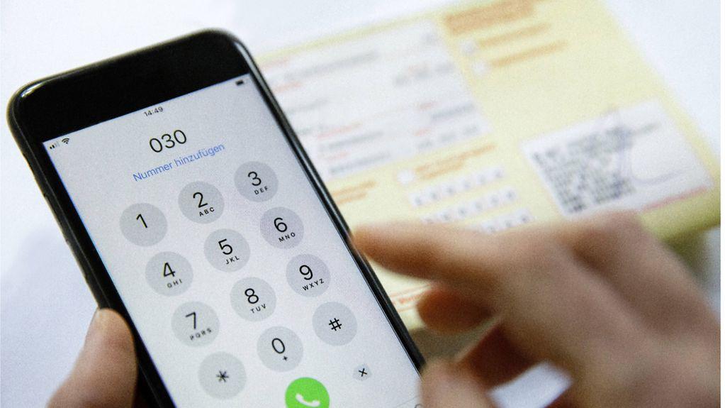 Ein Mobiltelefon und ein Krankenschein
