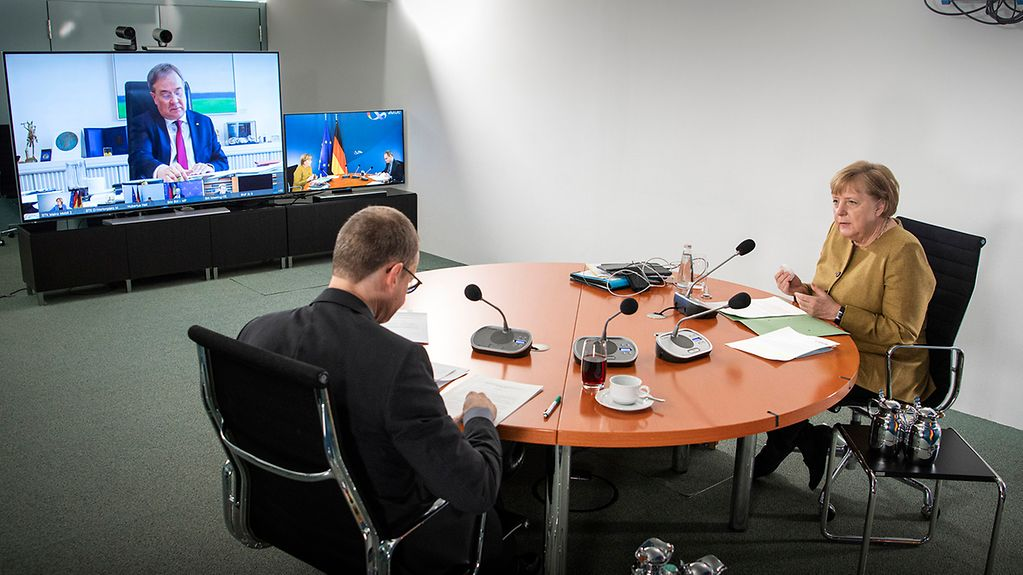 Chancellor Angela Merkel and Berlin's Governing Mayor attend the video conference in the Federal Chancellery. In the background Armin Laschet can be seen on a screen.