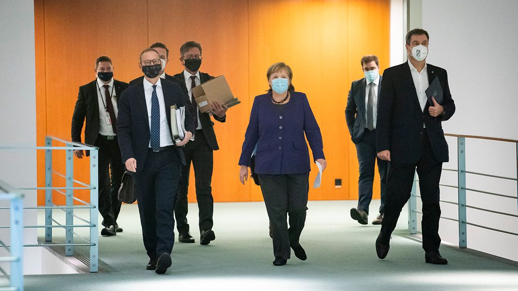 Chancellor Angela Merkel walks to a press conference between Michael Müller, Berlin's Governing Mayor and Markus Söder, Bavaria's State Premier.